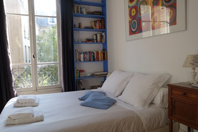 The bedroom features a large double bed and full-length windows